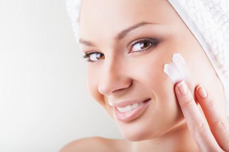 Close-up beautiful woman applying moisturizer cosmetic cream on face on light background Foto de archivo