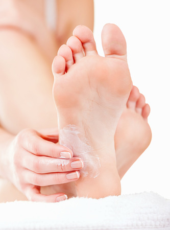 feet relaxing: Close-up woman applying moisturizer cosmetic cream on foot on light background Stock Photo