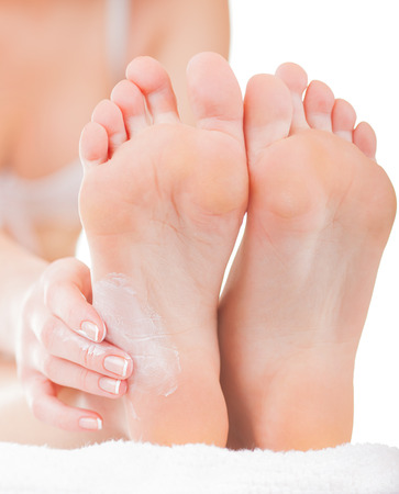Close-up woman applying moisturizer cosmetic cream on foot on light background Imagens