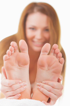 cosmetic cream: Close-up woman applying moisturizer cosmetic cream on foot on light background Stock Photo