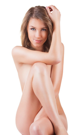 Beautiful young naked woman sitting on the floor - isolated on a white background