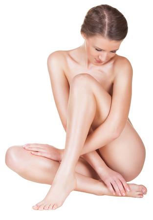 Красивая молодая обнаженная женщина, сидя на полу - изолированные на белом фоне