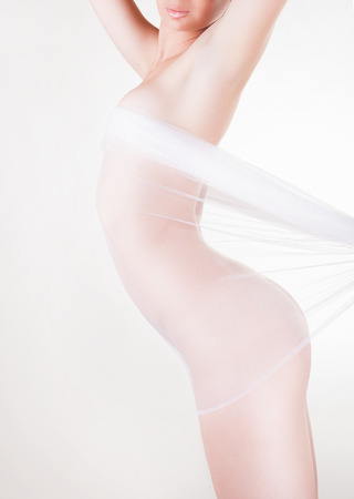 nude female buttocks: The body of a beautiful naked woman through the transparent fabric on a light background