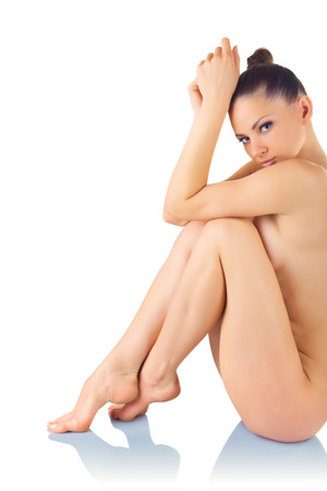 naked woman sitting: Beautiful young naked woman sits isolated on a white background