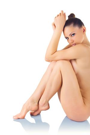 mujer desnuda sentada: Hermosa mujer desnuda joven se sienta aislado en un fondo blanco Foto de archivo