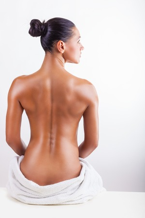 naked woman sitting: Beautiful back of a young woman on white background Stock Photo