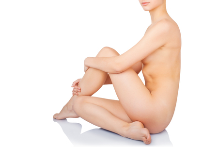 Young beautiful naked woman sits, isolated on a white background