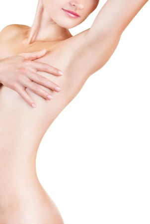 naked body: Young woman looking at her clean armpit isolated on white background