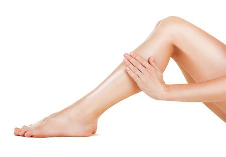 manos y pies: Aplicación de la crema hidratante en las piernas aisladas sobre fondo blanco Foto de archivo