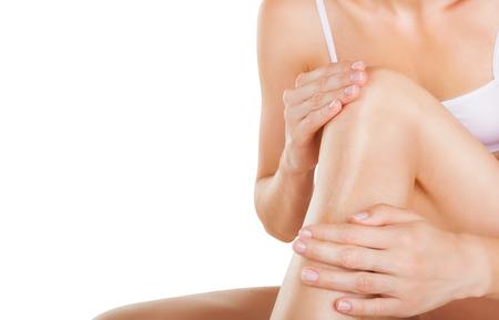 depilacion con cera: Aplicación de la crema hidratante en las piernas aisladas sobre fondo blanco Foto de archivo