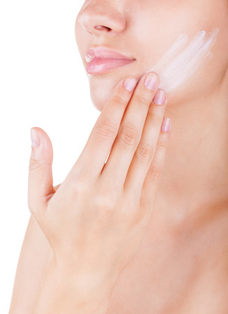 Close-up beautiful woman applying moisturizer cosmetic cream on face on light background Imagens