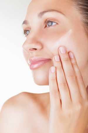 Close-up beautiful woman applying moisturizer cosmetic cream on face on light background photo