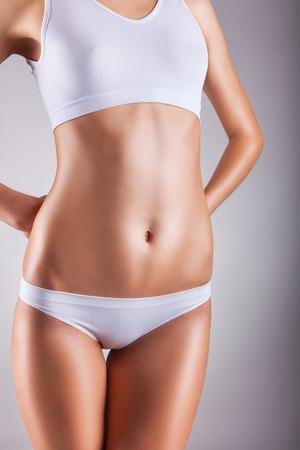 mujer celulitis: Cuerpo de mujer joven en bragas blancas sobre un fondo gris