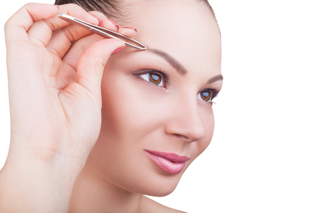 depilate: Beautiful young woman plucks eyebrows isolated on white background