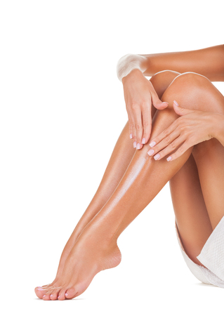 depilacion con cera: Aplicaci�n de la crema hidratante en las piernas aisladas sobre fondo blanco Foto de archivo