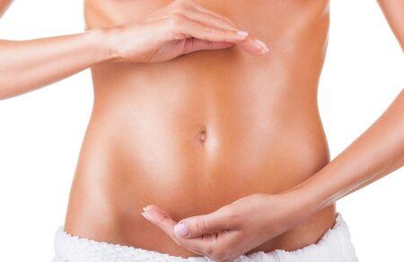 corps femme nue: Gros plan d'abdomen de la femelle et les mains de femme - symbole de la grossesse, isol� sur fond blanc Banque d'images
