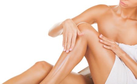 Anwendung Feuchtigkeitscreme Creme. Pflege für weibliche Beine isoliert auf weißem Hintergrund Standard-Bild