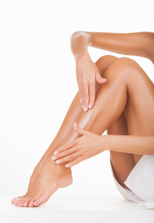 waxed legs: Applying moisturizer cream on the legs  isolated on white background Stock Photo