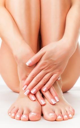 mujer desnuda: Pies femeninos hermosos y bien cuidados y los talones en el fondo blanco