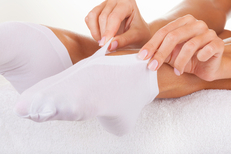 white socks: Woman wearing socks for foot care isolated on white background