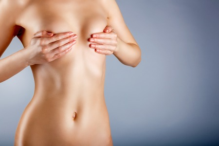 skin cancer: Slim woman covers her bare breasts on a blue background