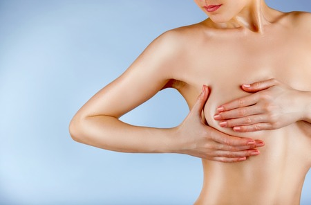mujer desnuda: Joven examinar sus senos para detectar signos de cáncer de mama aislados en un backgroundd azul