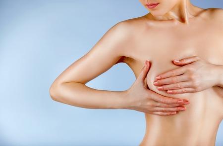 Junge Frau, die ihre Brüste auf Anzeichen von Brustkrebs auf einem blauen backgroundd isoliert untersuchen Standard-Bild