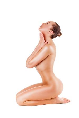 Schöne junge nackte Frau sitzt auf dem Boden - isoliert auf weißem Hintergrund