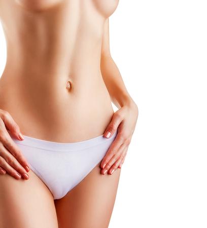 mujeres desnudas: Primer plano de una mujer joven y delgada en bragas aisladas sobre fondo blanco