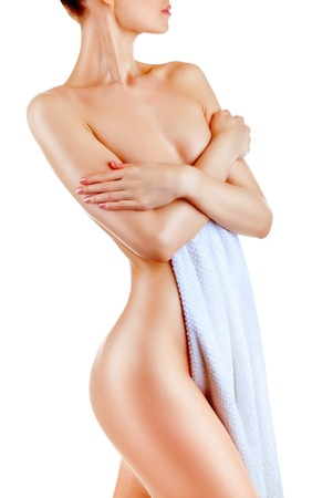 Well-groomed young woman in towel isolated on white background Stock Photo
