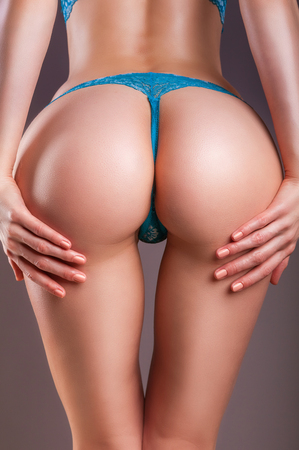 Attractive buttocks of young girl close-up on a gray background