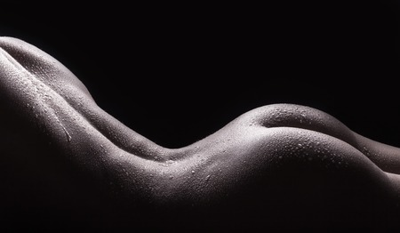 Beautiful buttocks of a nude young woman with wet body, closeup on dark background