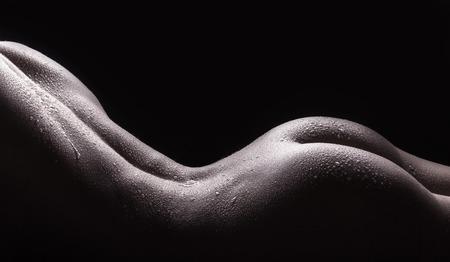 Hermosas nalgas de una joven mujer desnuda con el cuerpo mojado, primer plano sobre fondo oscuro Foto de archivo
