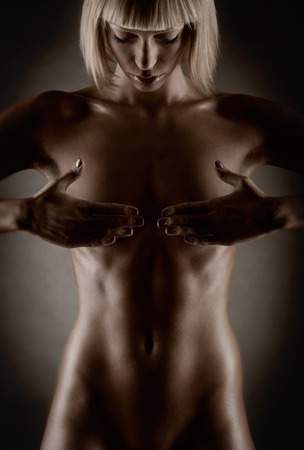 Beautiful naked female body on a dark background Stock Photo