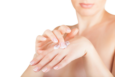 dermatology: Young woman applies cream on her hands on a white background. Focus on hands