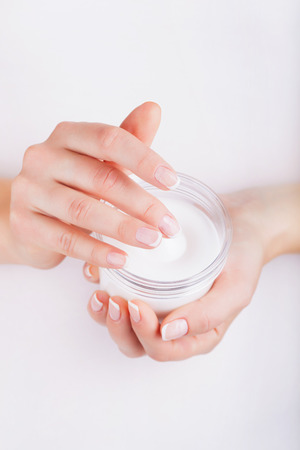 Woman applying cream on hands