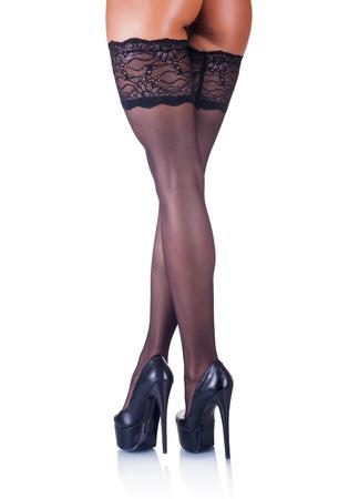 mujer sexy desnuda: Vista trasera de mujeres hermosas piernas en medias en tacones altos aislados sobre fondo blanco Foto de archivo