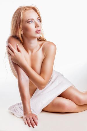 mujer desnuda sentada: Mujer joven en una toalla en el suelo sobre fondo blanco