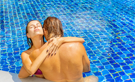 Happy couple bathing together in swimming pool photo
