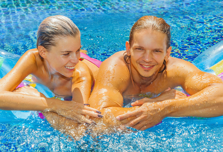 matress: Beautiful young couple having fun in pool