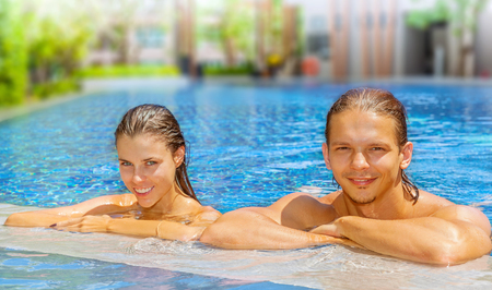 Beautiful smiling couple looking at camera while relaxing on the edge of a swimming pool. Focus on man photo