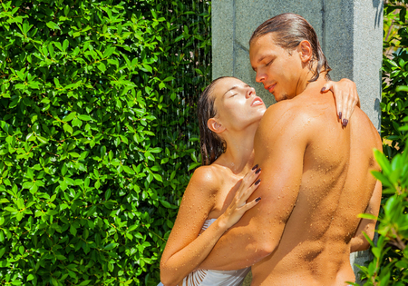 man shower: Happy smiling couple relaxing together in shower at health spa club Stock Photo