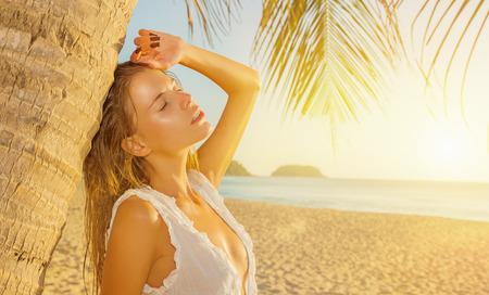 playas tropicales: Chica sexy en la playa durante la puesta de sol