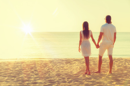 Happy young couple meets sunset on a tropical beach. Lovers in full body length on beach. Back rear view Standard-Bild