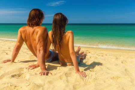 nue plage: Jeune couple assis ensemble sur le sable et la mer, regardant l'horizon r�ver