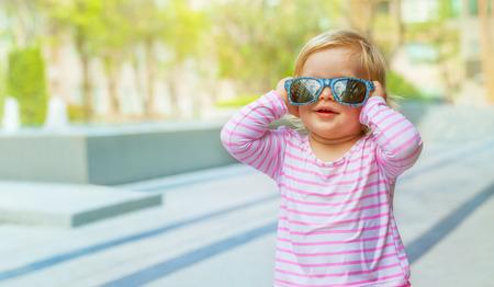 Bebé divertido en un traje de baño y gafas de sol Foto de archivo - 37260241