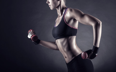 gym: Fitness girl with dumbbells on a dark background