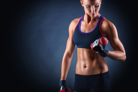 Fitness young woman with dumbbells on a dark background