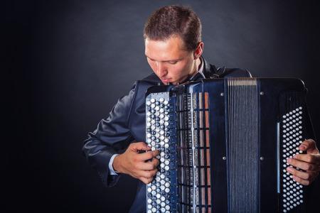 acordeón: Hombre joven con el acordeón sobre un fondo negro con copia espacio