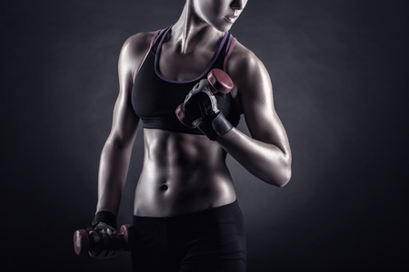 A young woman playing sports with weights on a dark background Standard-Bild